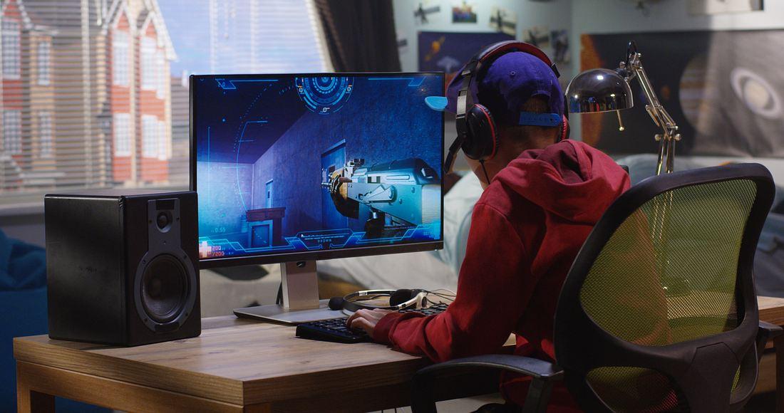 Junge sitzt vorm PC und spielt ein Videospiel