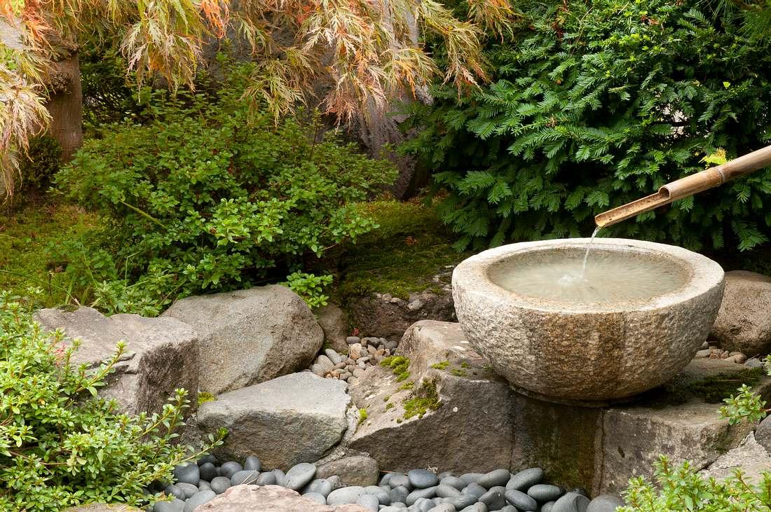 runder Gartenbrunnen aus Granit in idyllischem Garten