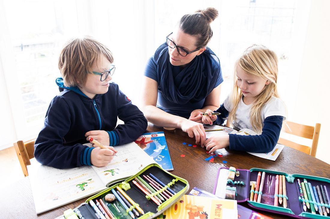 Mutter mit ihren Kindern bei den Schularbeiten Zuhause