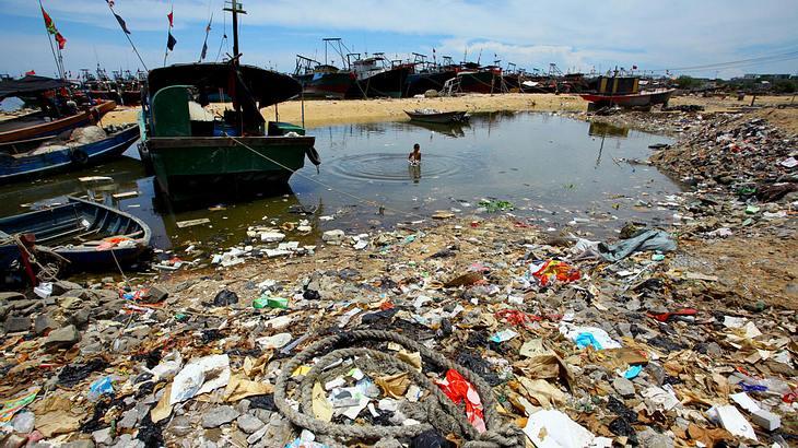Ein Junge schwimmt in einem verschmutzten See