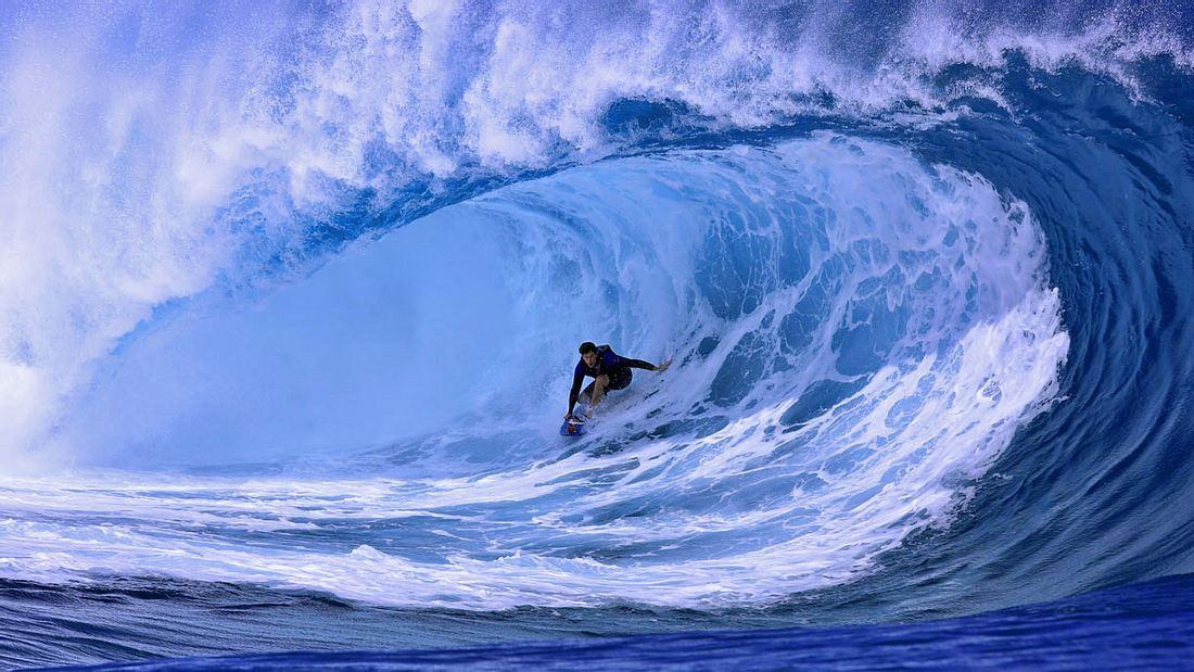 Ein Surfer reitet die Welle von Teahupoo