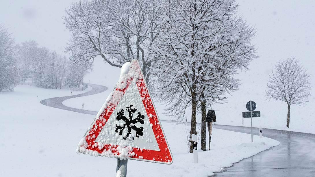 Überfrorene Straße mit Warnschild im Vordergrund - Foto: iStock / filmfoto