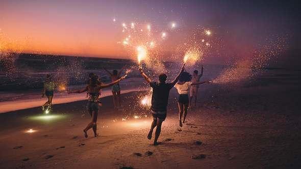 Menschen mit Wunderkerzen am Strand - Foto: iStock/wundervisuals
