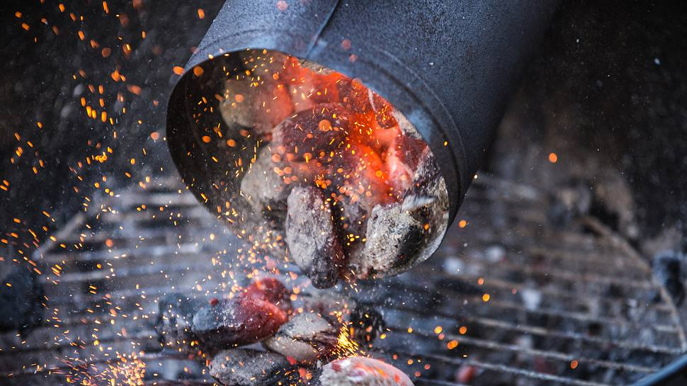 Anzündkamin schüttet durchgeglühte Holzkohle au den Grill - Foto: twpixels