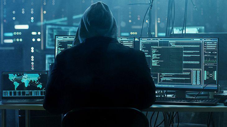 Hacker vor Computer-Bildschirmen