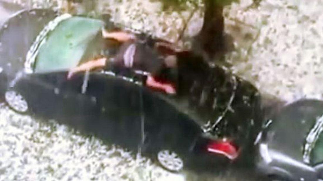 Blech-Bodyguard: Ein Mann schützt sein Auto mit vollem Körpereinsatz vor einem Hagelschauer