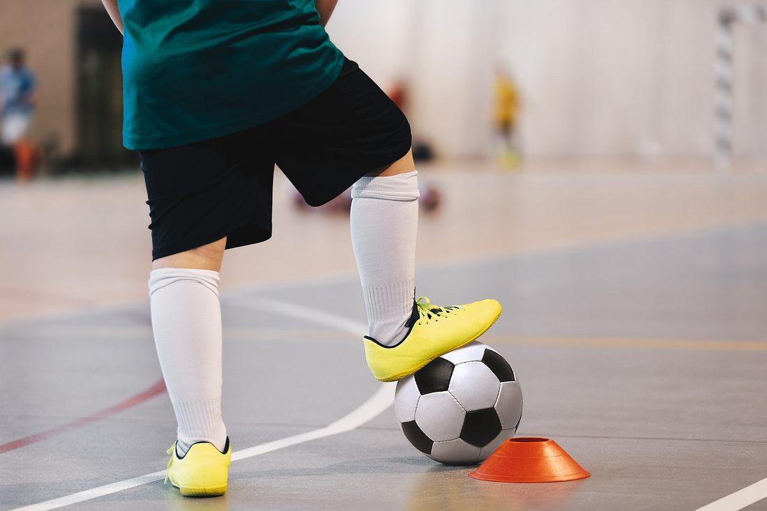 Ein Mann mit Hallenfußballschuhen und Fußball in einer Turnhalle