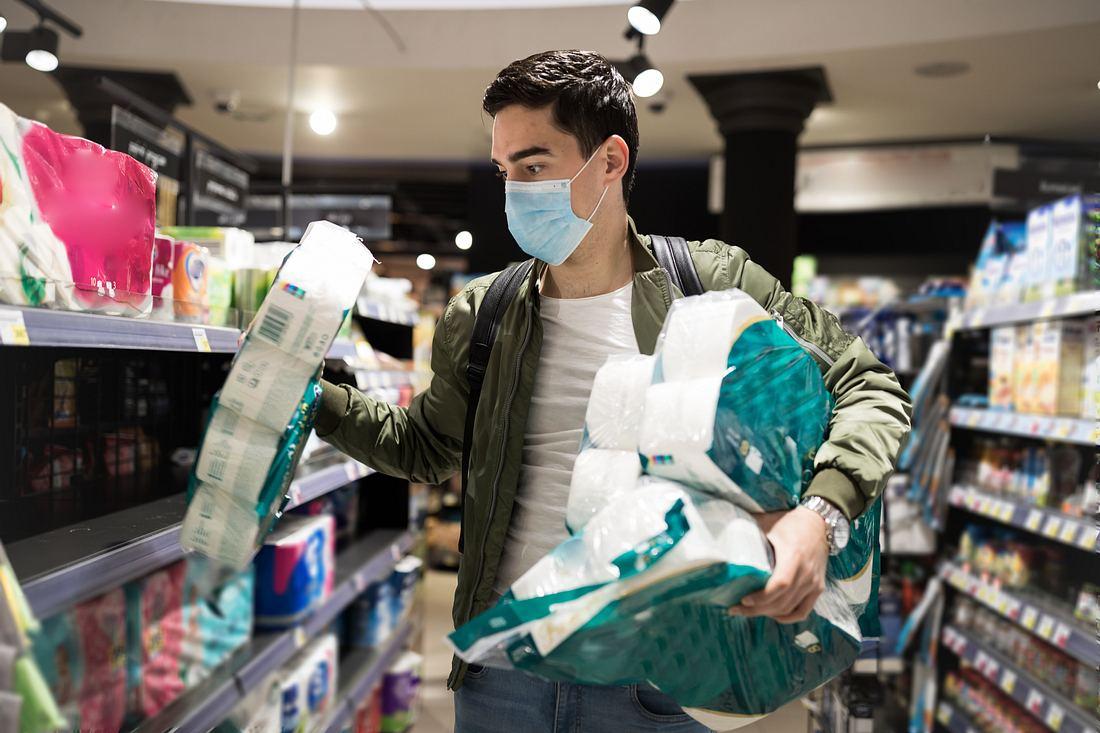 Junger Mann mit Mundschutzmaske kauft viel Klopapier