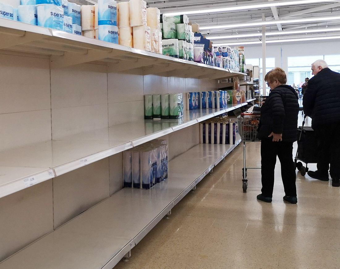 Zwei Supermarkt-Kunden stehen vor einem leeren Verkaufsregal
