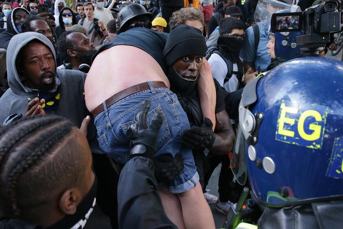 Patrick Hutchinson trägt einen Demonstranten