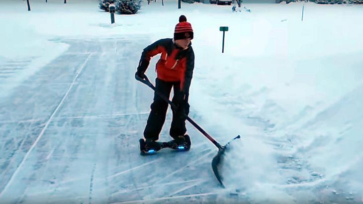 Ein US-Teenager befreit eine Auffahrt mithilfe eines Hoverboards und einer Schneeschippe von Schnee