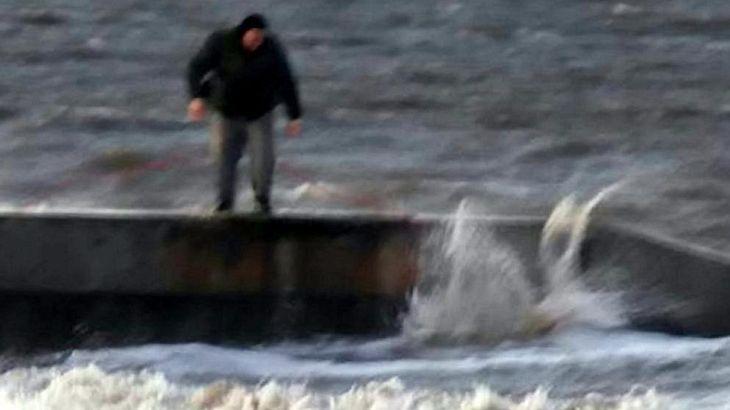Ein Mann wirft seinen Hund in die eiskalte Nordsee