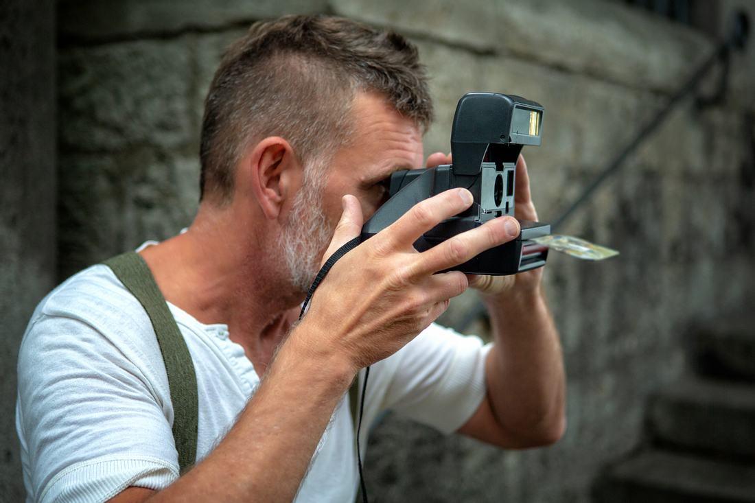 Bärtiger Mann mit Sofortbildkamera