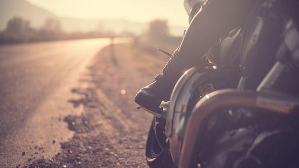 Seitenansicht auf einen Biker auf der Straße - Foto: iStock/MilosStankovic