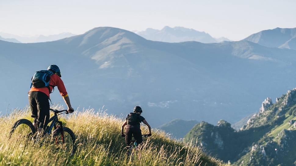 Mountain bikers ride down grassy mountain ridge - Foto: iStock / AscentXmedia