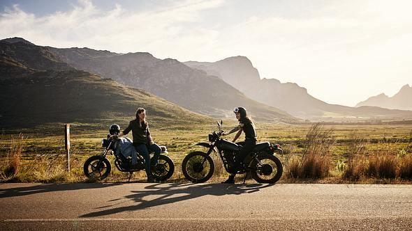 Zwei Motorräder stehen am Straßenrand vor den Bergen. - Foto: iStock/pixdeluxe