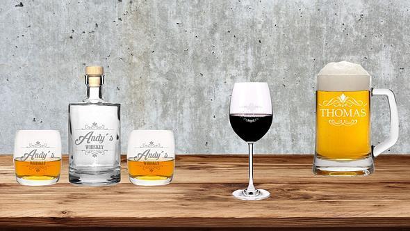 Gläser mit Gravur auf Holzbank vor grauem Hinter