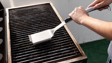 Grill wird mit Grillbürste gereinigt