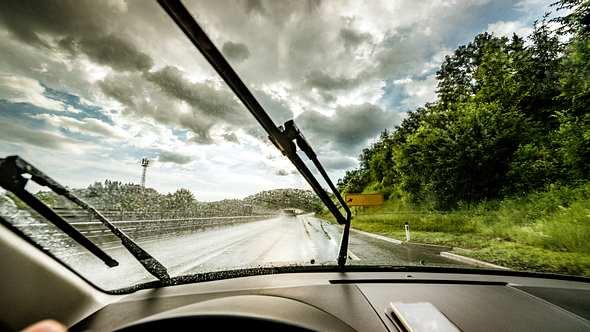 Blick aus der Frontscheibe eines Autos mit Scheibenwischer bei Regen