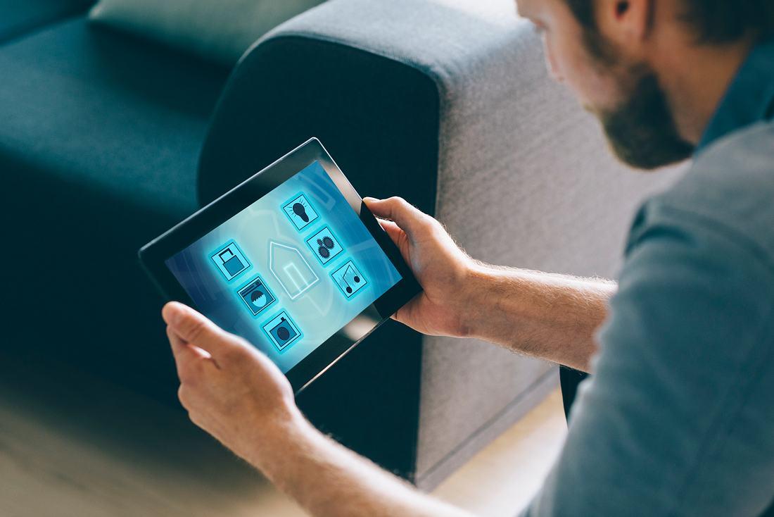 Mann konfiguriert seine Smart Home Geräte auf I-Pad