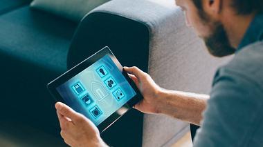 Mann konfiguriert seine Smart Home Geräte auf I-Pad - Foto: iStock/mikkelwilliam