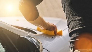 Ein Mann reinigt seine Motorhaube