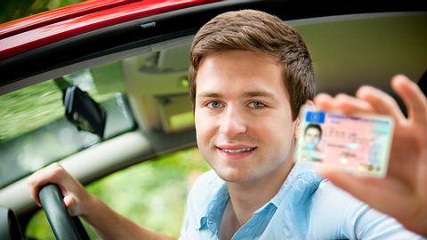 Junger Mann zeigt freudestrahlend seinen Führerschein - Foto: iStock / AlexRaths