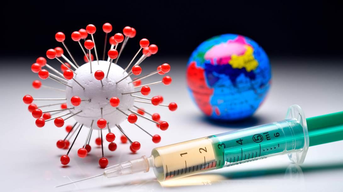 Ein Coronavirus-Modell, eine Erdkugel und eine Impfspritze - Foto: imago images / Christian Ohde