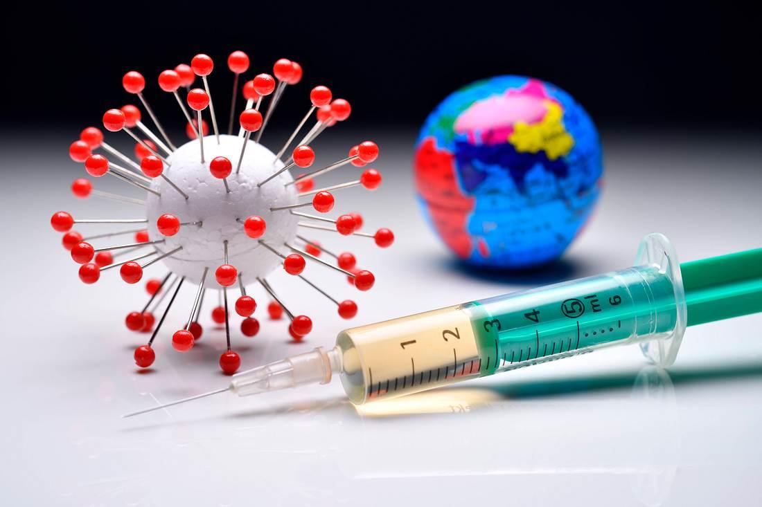 Ein Coronavirus-Modell, eine Erdkugel und eine Impfspritze