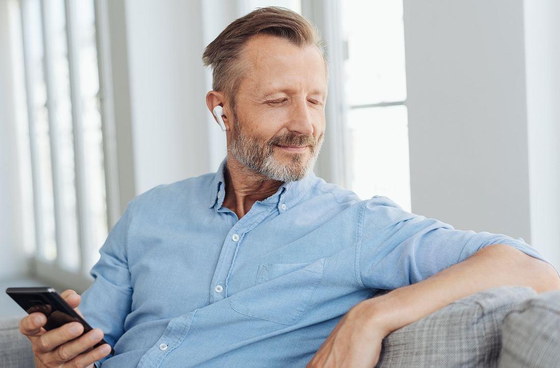 Mann mit True Wireless-Kopfhörern im Ohr und Handy in der Hand