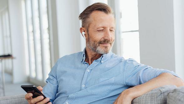 Mann mit True Wireless-Kopfhörern im Ohr und Handy in der Hand - Foto: iStock / stockfour