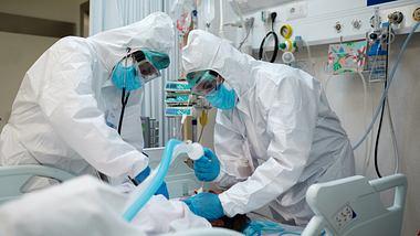 Mediziner kümmern sich um einen Corona-Patienten - Foto: iStock / Tempura