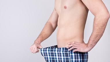 Mann mit karierter Boxershorts, die er am Bund mit einer Hand vom Bauch wegzieht - Foto: iStock/diephosi
