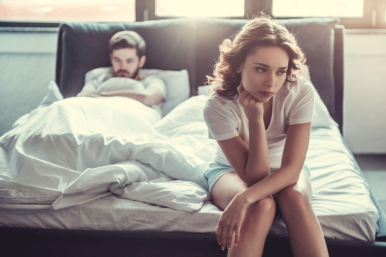 Mann liegt traurig im Bett, Frau sitzt auf der Bettkante und guckt genervt
