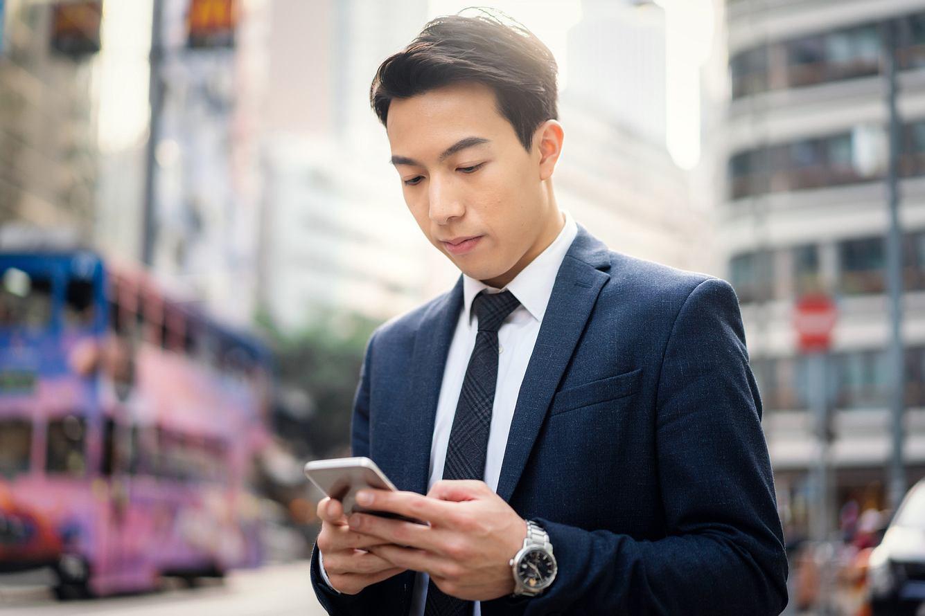Junger Chinese mit Handy
