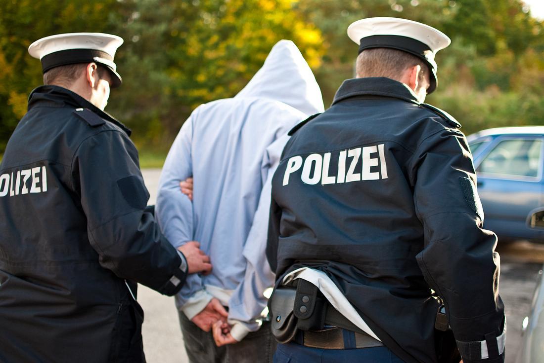 Junger Mann wird von Polizei abgeführt