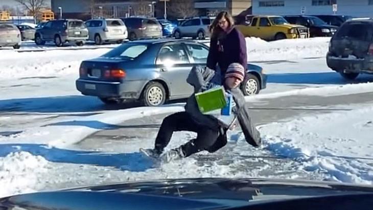 Ein Vater filmt, wie Kinder vor der Schule seiner Tochter auf der vereisten Straße ausrutschen