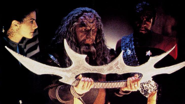 Der Klingone Kor hält das Bat'leth des Klingonen-Oberhaupts Kahless in seinen Händen.