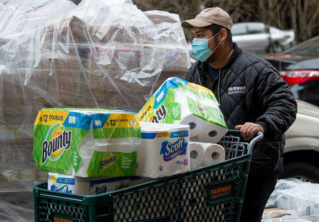 Mann mit Einkaufswagen voller Klopapier
