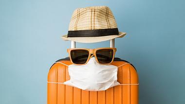 Hut, Sonnenbrille, Corona-Maske und Koffer - Foto: iStock / zoff-photo