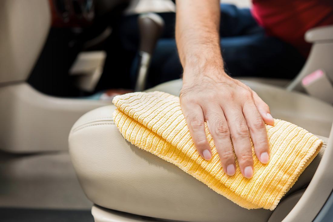 Ein Mann reinigt Ledersitze mit einem Mikrofasertuch
