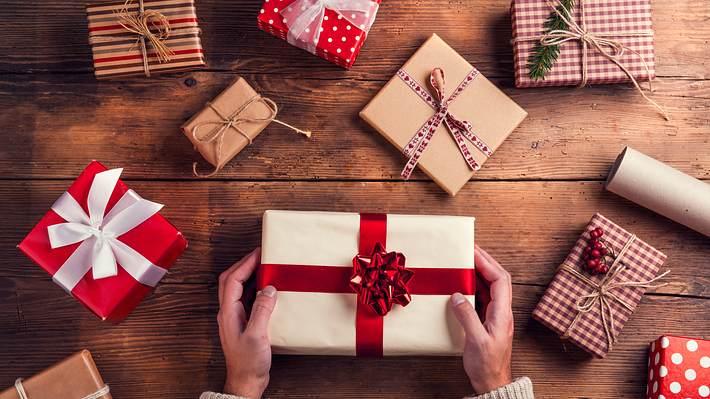 Zahlreiche Weihnachtsgeschenke liegen auf einem Holztisch - Foto: iStock/Halfpoint