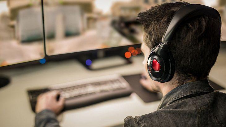 Mann sitzt am PC und spielt