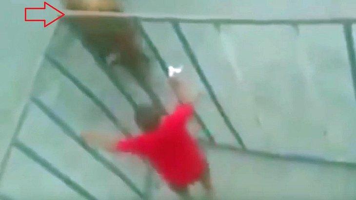 Ein Mann mit roten T-Shirt provoziert einen Stier aus einem Käfig heraus