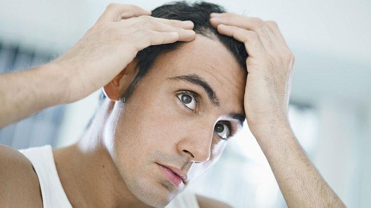 Mann inspiziert seine Haare