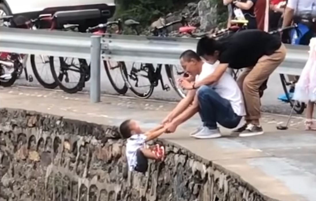 Mann hält Kind über Abgrund