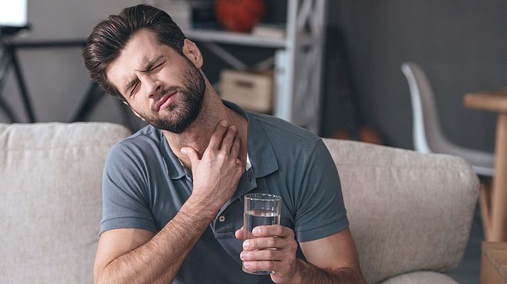 Mann leidet unter Halsschmerzen