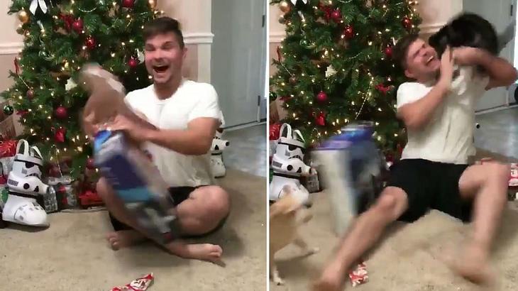 Eine Katze attackiert einen mann, der zu Weihnachten eine PlayStation 4 auspackt