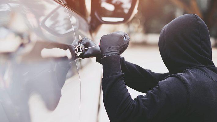 Mann bricht Autotür auf - Foto: iStock/Rattankun Thongbun