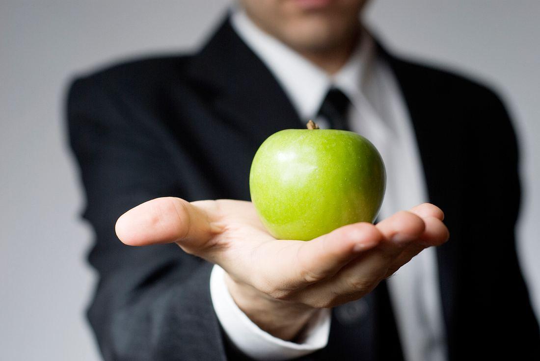 Ein Mann hält einen grünen Apfel in die Kamera